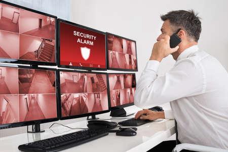 Foto de Male Operator Using Walkie-talkie While Monitoring Multiple CCTV Footage - Imagen libre de derechos