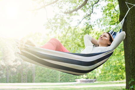 Photo pour Young Happy Woman Relaxing In Hammock At Garden - image libre de droit