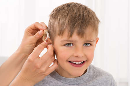Foto de Close-up Of A Doctor Fitting Hearing Aid On Smiling Boy's Ear - Imagen libre de derechos