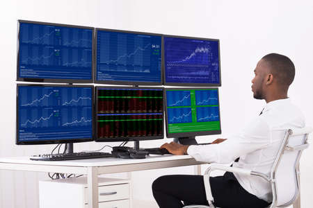 Photo pour Businessman Analyzing Data Displayed On Multiple Computer Screens In Office - image libre de droit