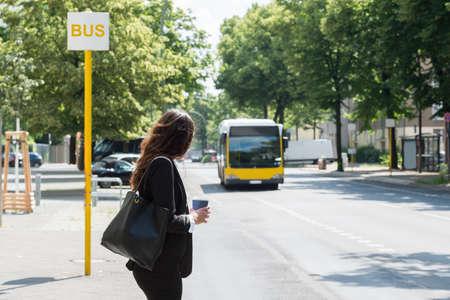 Foto de Young Businesswoman With Disposal Cup Waiting For Bus - Imagen libre de derechos