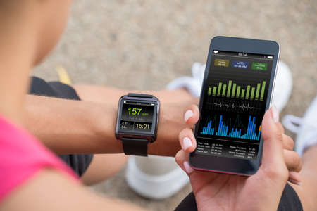 Foto per Female Runner Looking At Her Mobile And Smart Watch Heart Rate Monitor - Immagine Royalty Free