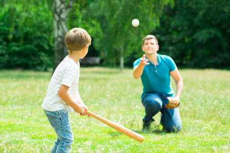 Photo for Little Boy Playing Baseball With His Father In Park - Royalty Free Image