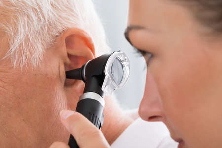 Foto de Close-up Of Female Doctor Examining Patient's Ear With Otoscope - Imagen libre de derechos