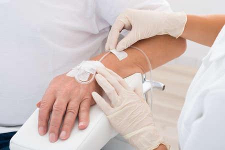 Foto de Close-up Of Doctor's Hand With Iv Drip Inserted In Patient's Hand - Imagen libre de derechos