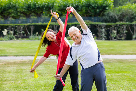 Photo for Happy Senior Couple Exercising With Yoga Belt In Park - Royalty Free Image