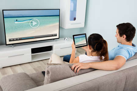 Photo pour Young Couple Connecting Television Channel Through Wi-fi On Digital Tablet At Home - image libre de droit