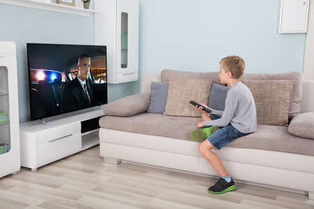 Photo for Kid with remote control sitting on couch watching movie on tv - Royalty Free Image