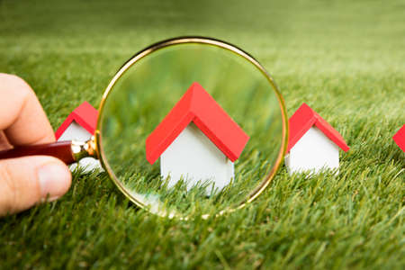 Photo pour Person Hands With Magnifying Glass Inspecting A Model House On Grassy Field - image libre de droit