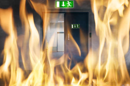 Foto de Close-up Of Fire Burning Near An Emergency Exit Door Of The Building - Imagen libre de derechos
