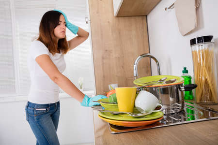Photo pour Young Exhausted Woman Standing In The Kitchen Near Utensil In The Sink - image libre de droit