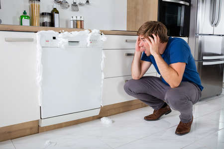 Foto de Young Man Shocked On Seeing Foam Coming Out Of Dishwasher At Home - Imagen libre de derechos