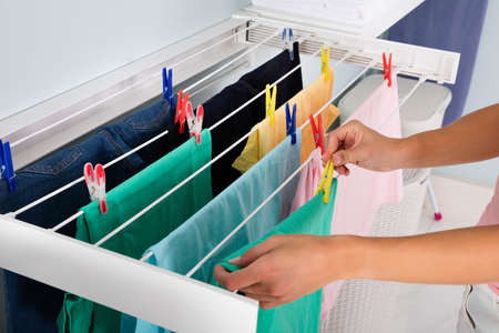 Photo pour Close-up Of Woman Hanging Wet Clean Cloth On Clothes Line In laundry Room - image libre de droit