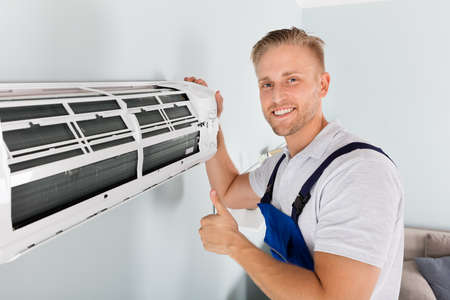 Photo pour Smiling Male Electrician Gesturing Thumbs Up Near Air Conditioner - image libre de droit