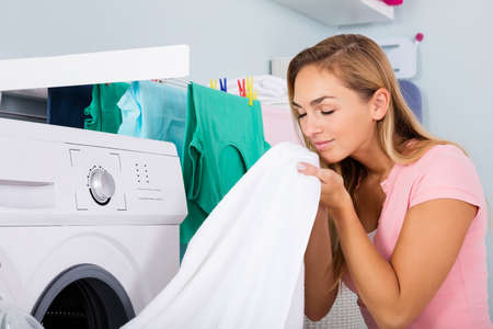 Foto de Woman Smelling Clean Clothes Near The Electronic Washer At Laundry Room - Imagen libre de derechos