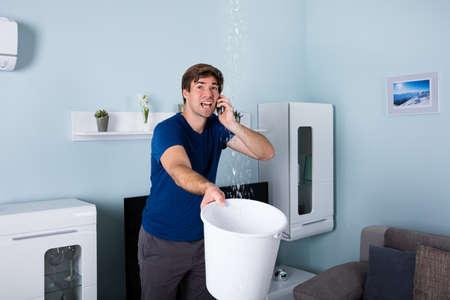Foto de Worried Man Calling Plumber While Leakage Water Falling Into Bucket At Home - Imagen libre de derechos