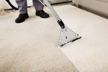 Photo pour Close-up Of A Person Cleaning Carpet With Vacuum Cleaner - image libre de droit
