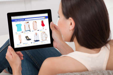 Photo pour Close-up Of Woman Doing Online Shopping On Digital Tablet At Home - image libre de droit