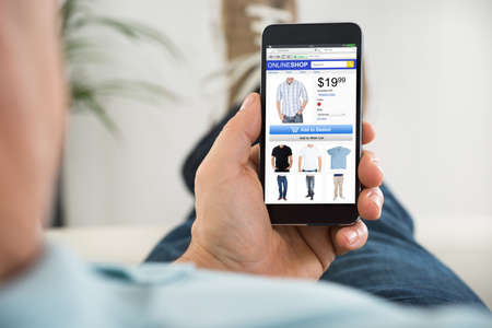 Photo for Close-up Of Man Buying Cloth While Shopping Online On Smartphone - Royalty Free Image