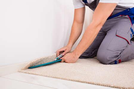 Photo pour Close-up Of A Craftsman Fitting Carpet On Floor With Cutter - image libre de droit