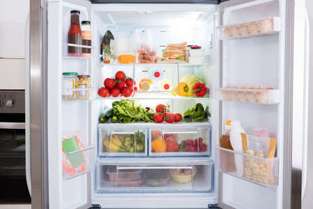 Photo pour Open Refrigerator Filled With Fresh Fruits And Vegetable - image libre de droit