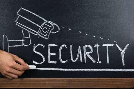 Photo pour Close-up Of A Person Hand Showing Security Concept On Blackboard - image libre de droit