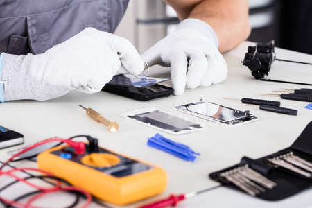 Photo pour Close-up Of Technician Hand Wearing Glove Fixing Cellphone - image libre de droit