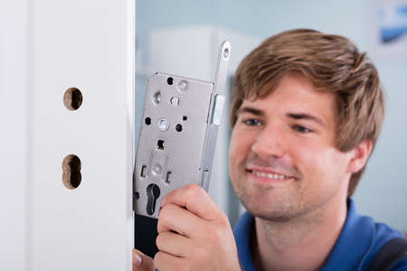 Foto de Close-up Of Man's Hand Installing Door Lock At Home - Imagen libre de derechos