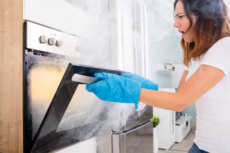 Photo pour Young Unhappy Woman Opening Door Of Oven With Full Of Smoke - image libre de droit
