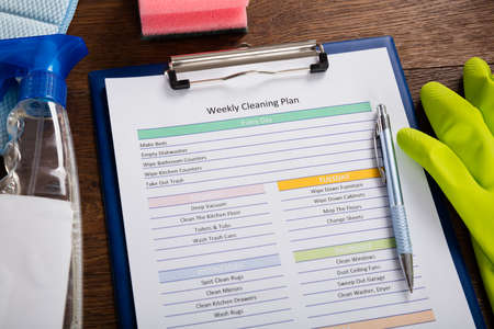 Photo pour High Angle View Of Weekly Cleaning Plan Form With Pen On Clipboard - image libre de droit