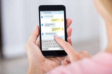 Foto de Close-up Of A Person Sending Text Message Using Mobile Phone - Imagen libre de derechos