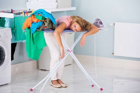 Photo pour Young Tired Woman Sleeping On Ironing Board Next To Pile Of Clothes At Home - image libre de droit