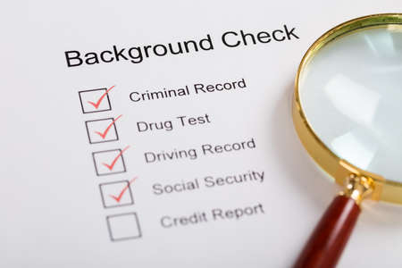 Photo pour High Angle View Of Magnifying Glass Over Background Check Form - image libre de droit