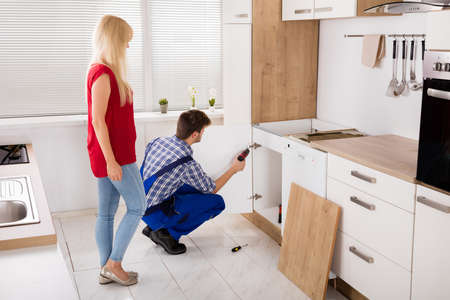 Photo pour Repairman Fixing Or Installing The Furniture Door Of The Kitchen Sink In Front Of Woman - image libre de droit