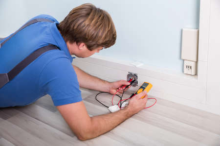 Photo pour Electrician Checking Socket Voltage Using Multimeter In A Wall Fixture - image libre de droit