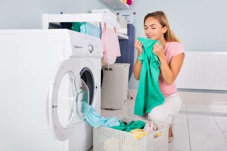 Foto de Young Smiling Woman Smelling Clothes After Washing In Washing Machine At Utility Room - Imagen libre de derechos