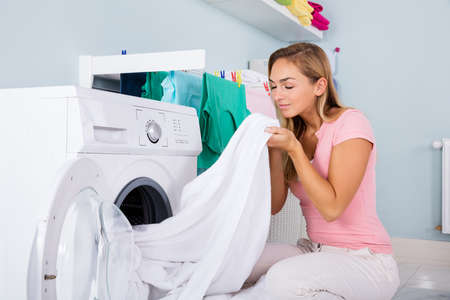 Foto de Young Woman Smelling Clean Clothes Near The Electronic Washer At Laundry Room - Imagen libre de derechos