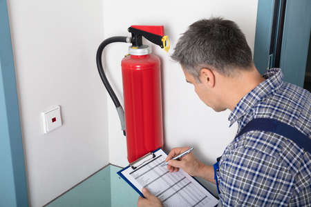 Photo pour Close-up Of A Male Professional Checking A Fire Extinguisher Using Clipboard - image libre de droit