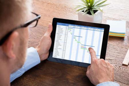 Foto de Businessman Working On Gantt Chart On Digital Tablet At Wooden Desk - Imagen libre de derechos