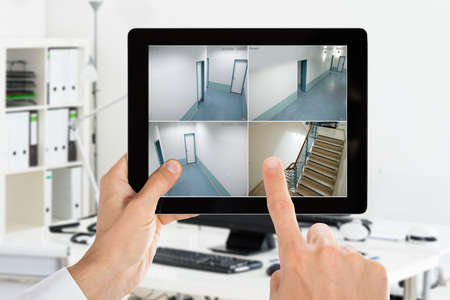 Photo pour Man Monitoring Camera CCTV Security Videos On Digital Tablet At Office - image libre de droit