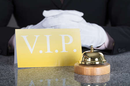 Photo pour Close-up Of A Waiter Hand Near Service Bell And VIP Card On Desk - image libre de droit