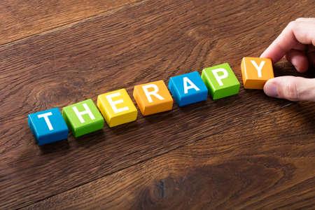 Foto de Close-up Of A Therapy Concept On Colorful Block At Wooden Desk - Imagen libre de derechos