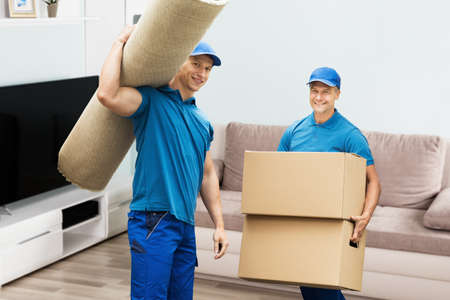 Photo for Portrait Of A Two Male Workers Carrying Carpet And Cardboard Boxes In House - Royalty Free Image