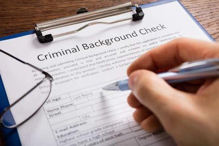 Photo pour Close-up Of Person Hand Filling Criminal Background Check Application Form - image libre de droit