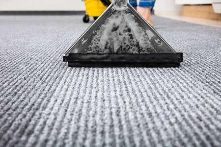 Photo pour Close-up Of A Cleaning Carpet With Vacuum Cleaner - image libre de droit