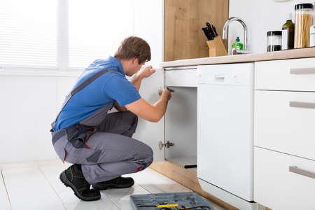 Photo pour Repairman In Overalls Repairing Cabinet Hinge In Kitchen - image libre de droit