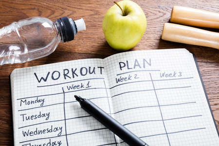 Foto de High Angle View Of A Workout Plan In Notebook At Wooden Desk - Imagen libre de derechos