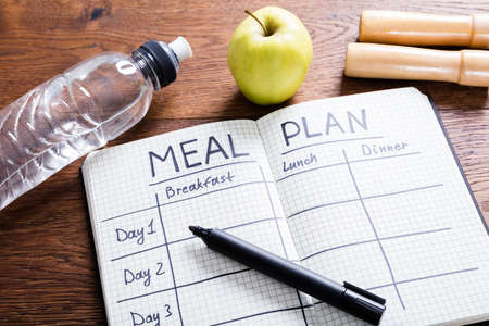 Photo pour High Angle View Of A Meal Plan Concept On Wooden Desk - image libre de droit