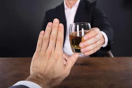 Foto de Businessman Hand Rejecting A Glass Of Whiskey Offered By Businessperson - Imagen libre de derechos