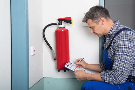 Foto de Close-up Of A Male Professional Checking A Fire Extinguisher Using Clipboard - Imagen libre de derechos